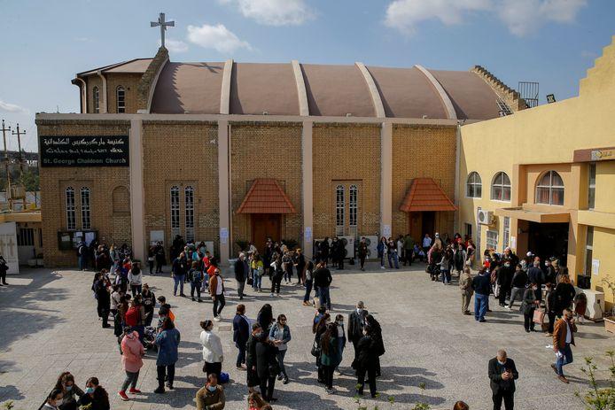 Christelijke families verzamelen zich buiten de St. George Chaldean Kerk in Bagdad in afwachting van de komst van paus Franciscus.