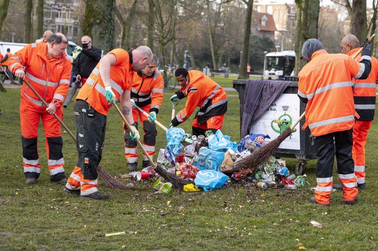 Opruimen in het Amsterdamse Vondelpark. De politie greep eerder in omdat het in het park te druk was en de coronamaatregelen niet werden nageleefd. Beeld ANP