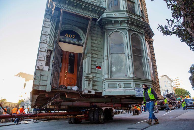 Het Victoriaanse 'Englander House' in San Francisco moet na 139 jaar plaatsmaken voor een nieuwbouwproject van 48 woningen. Een oplegger bracht het monument zondag naar een nieuw onderkomen, zes straten verderop.  Beeld REUTERS