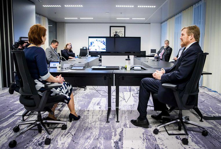Koning Willem-Alexander neemt deel aan een videoconferentie met buitenlandse ambassades tijdens een werkbezoek. Juist nu veel meer communicatie digitaal verloopt, is de beveiliging hiervan extra belangrijk, volgens de Rekenkamer. Beeld ANP