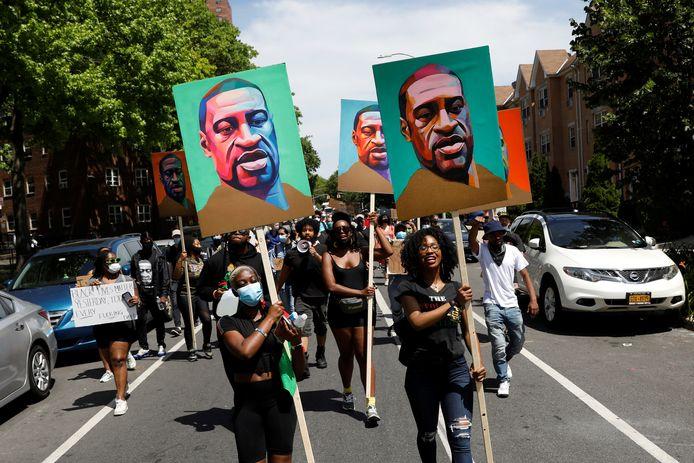 Betogers met een protestbord met de beeltenis van George Floyd.