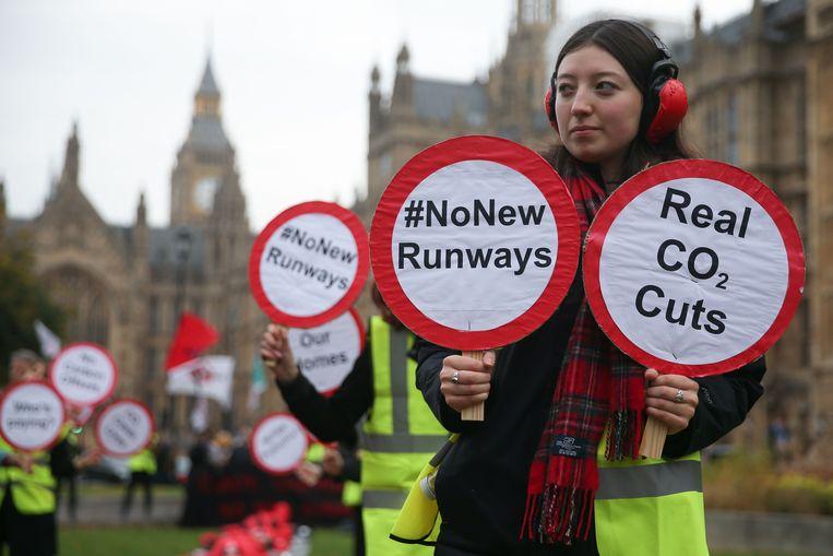 Voor het Britse parlement wordt dinsdag geprotesteerd tegen tegen de aanleg van een derde landingsbaan bij Heathrow.  Beeld AFP