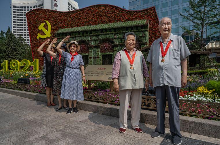 Chinezen laten zich fotograferen voor het feestelijk opgestelde partijlogo in Peking. Beeld Getty Images
