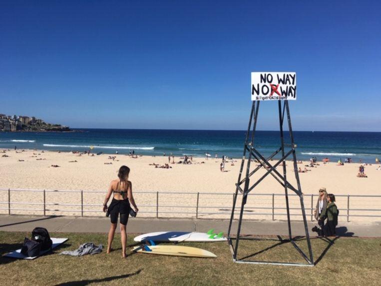 Het Noorse energiebedrijf Equinor wil in de Great Australian Bight gaan boren naar olie, maar daar steken de Australische surfers een stokje voor: 'No Way Norway' staat te lezen op een bord: 'echt niet, Noorwegen'.  Beeld BELGAONTHESPOT