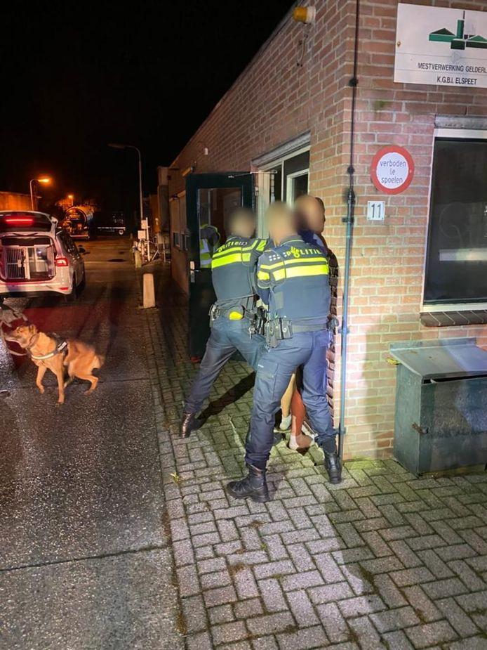 Een aantal politieagenten houden de man in bedwang.