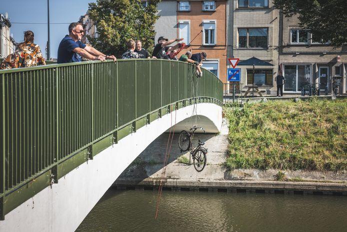 Magneetvissers op de fietsbrug aan de Groendreef halen heel wat fietswrakken en ander metaal uit het water