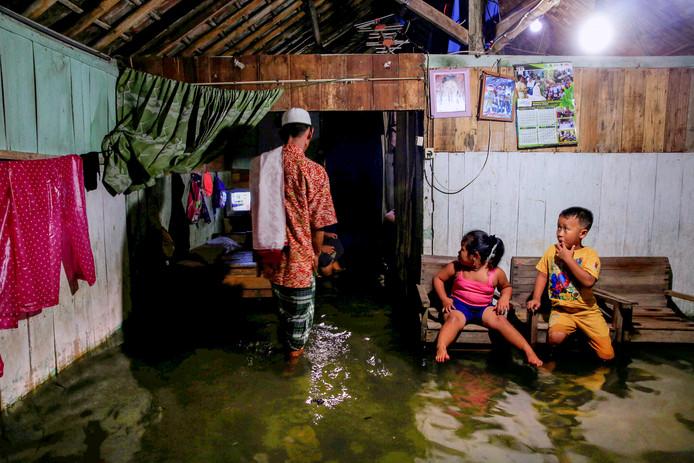 Een vader door zijn ondergelopen huis, in Sriwulan Indonesie, terwijl zijn kinderen hem na kijken. Door de klimaatverandering en vernietiging van het kustlandschap zakt de grond waardoor het zeewater bij vloed steeds verder landinwaarts stroomt met als gevolg dat de huizen aan de kust onderlopen. Foto: Beawiharta