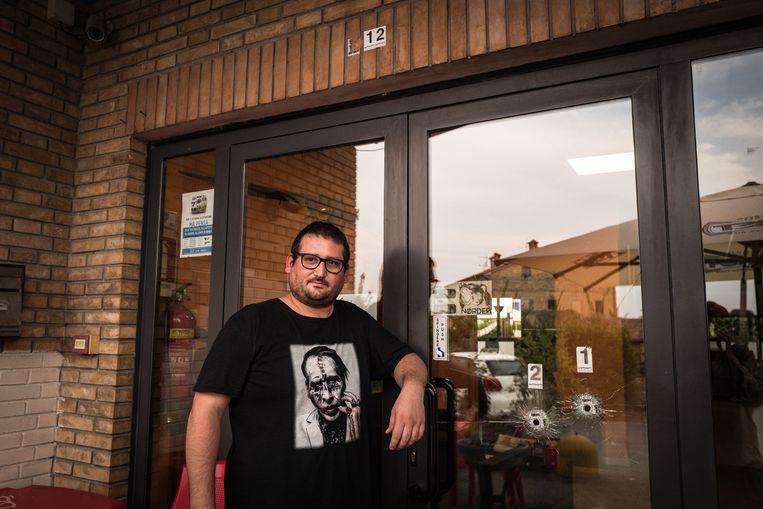 Eigenaar Roberto Tartabini bij de kogelgaten in de deur van zijn bar H7 in Casette Verdini, waar Luca Traini als uitsmijter werkte en op migranten schoot. Beeld Nicola Zolin