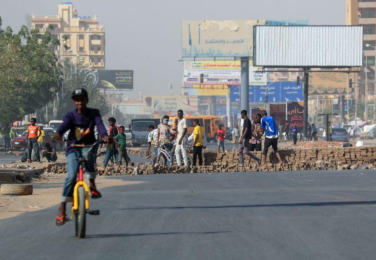 Soedanese actievoerders blokkeren de weg met bakstenen in Khartoem als protest tegen de stijgende prijzen.  Beeld AFP
