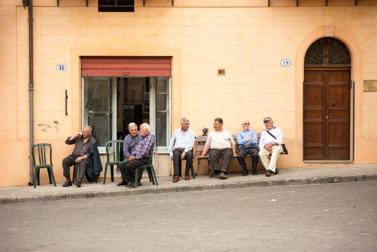 De dorpsoudsten overschouwen de 'passeggiata', het Italiaanse ritueel waarbij iedereen 's avonds buitenkomt en langs de centrale piazza flaneert.  Beeld Dieter Moeyaert