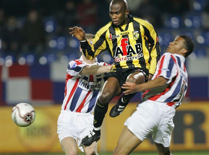Matthew Amoah torent in het shirt van Vitesse in 2005 hoog uit boven twee spelers van Willem II.