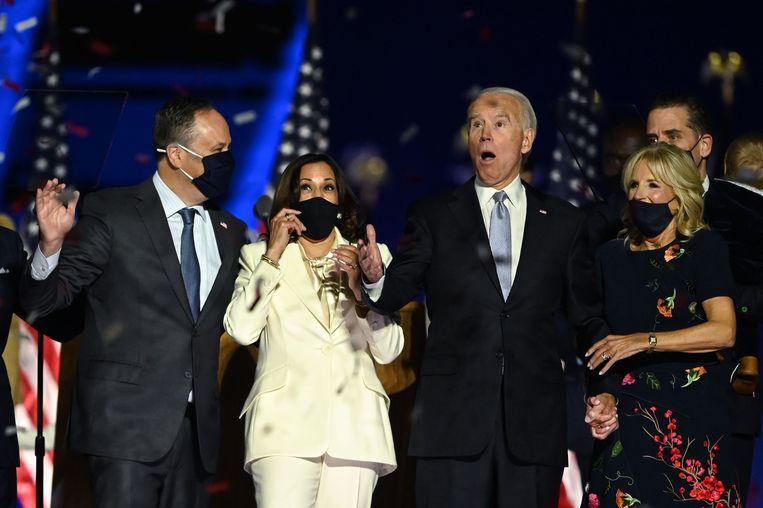 Joe Biden en Kamala Harris krijgen confetti over zich heen, samen met hun partners Jill Biden en Douglas Emhoff. Beeld AFP