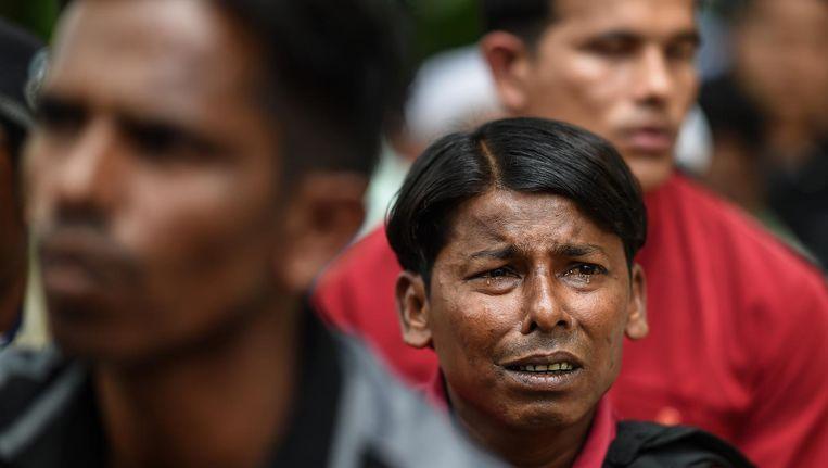 Een man huilt nadat hij is opgepakt door de Maleisische politie tijdens de protesten. Beeld AFP