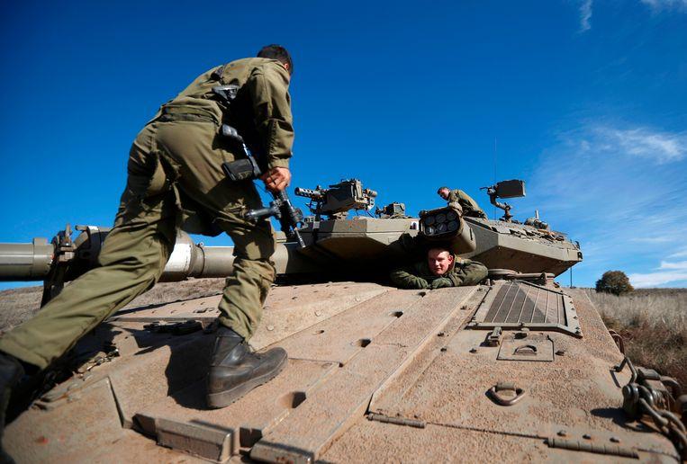Een Israëlische soldaat loopt op een tank tijdens een militaire oefening in de door Israël bezette Golanhoogte nabij Syrië.  Beeld AFP