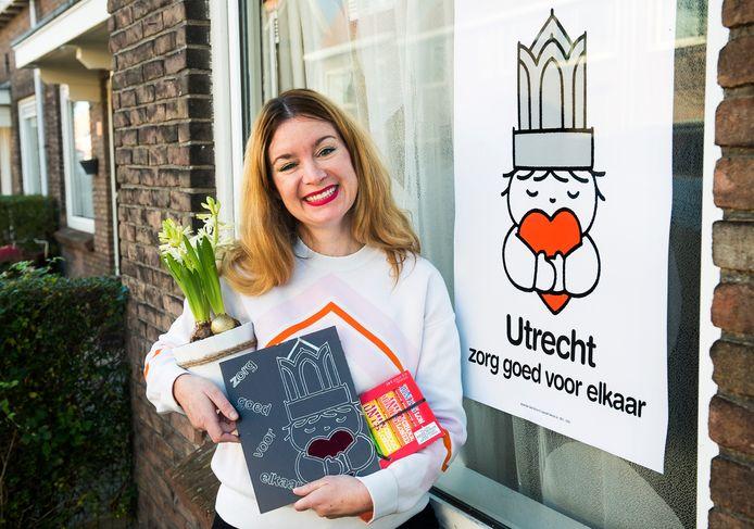 Cultureel marketeer Marije Lieuwens met een aantal cadeaus, die ze kreeg in ruil voor de door haar bedachte poster 'Utrecht zorg goed voor elkaar'.