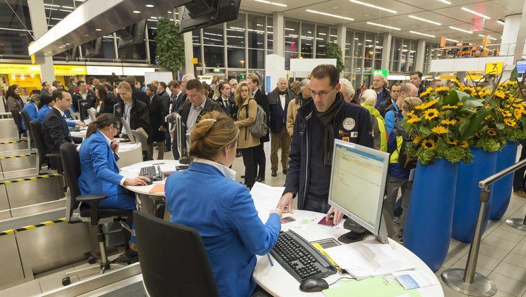 Passagiers staan in de rij om in te checken op Schiphol. Beeld ANP