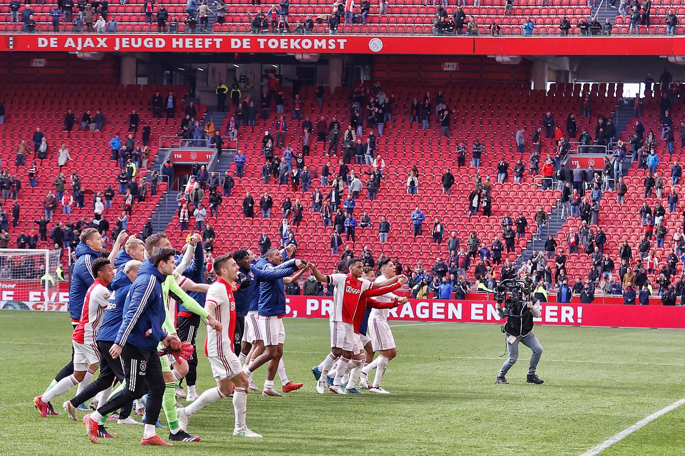 De spelers van Ajax vieren het officieus binnenhalen van de titel met hun supporters.