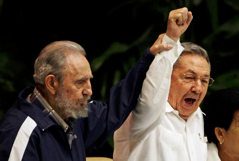 Fidel Castro (links) houdt de hand van zijn broer Raúl omhoog tijdens een congres van de Communistische Partij in 2011.