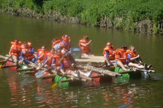 Enkele jongeren op een zelfgebouwd vlot op de Dender.