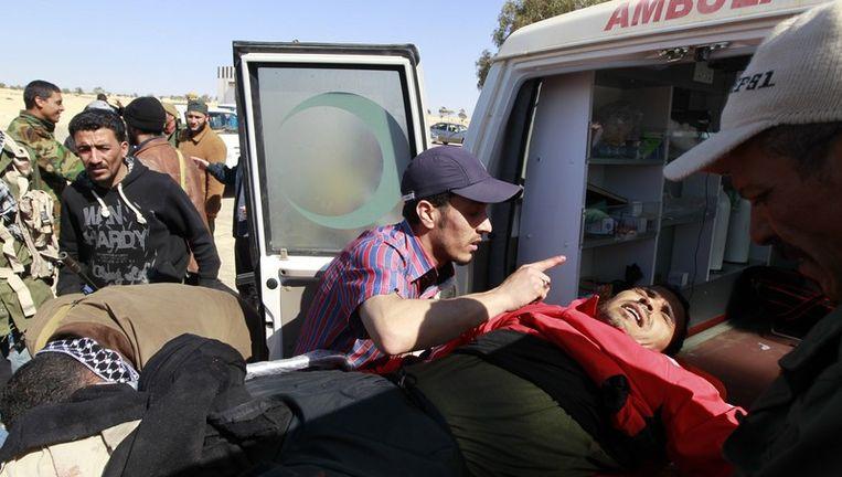 Rebellen dragen een gewonde man in een ambulance in Ajdabiyah. Beeld reuters