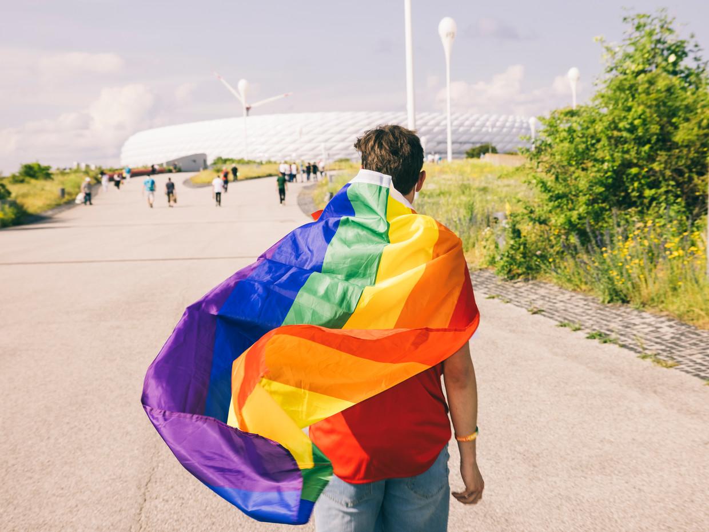 Voetbalsupporter met regenboogvlag woensdag bij het stadion in München voor de wedstrijd Duitsland-Hongarije. Beeld Janek Stroisch