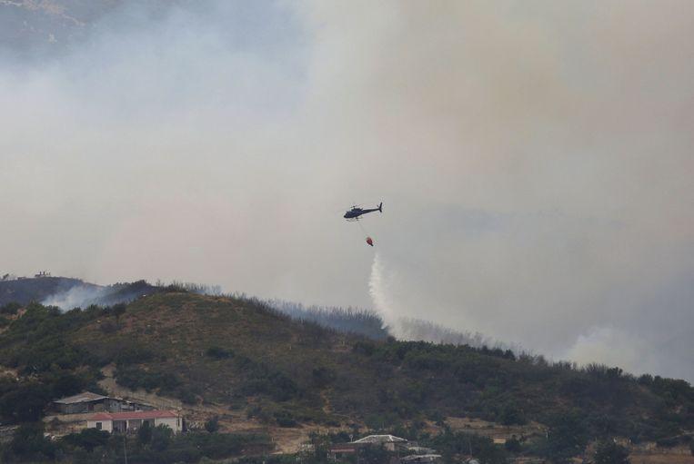 Een blushelikopter gooit water over het dorp Gjorm, vlakbij de stad Vlora in Albanië. Beeld AFP