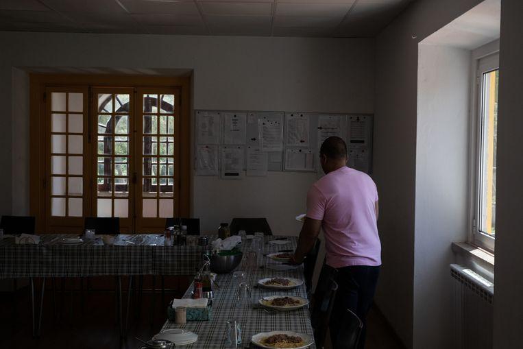 Een man dekt de tafel in de afkickkliniek Ares do Pinhal in Rinchoa, op 15 kilometer afstand van Lissabon. Beeld Gonçalo Fonseca