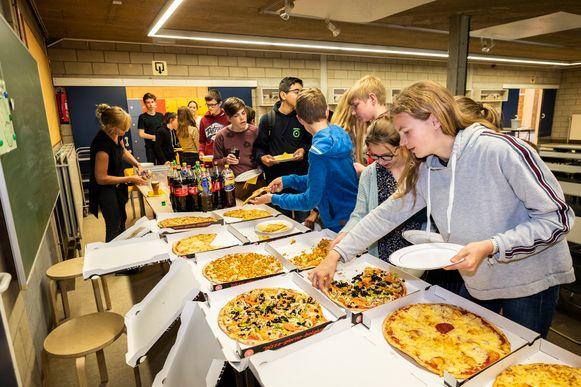 De leerlingen smullen van het pizzabuffet.