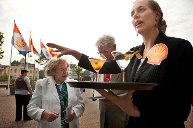 Protest van Milieudefensie tijdens een aandeelhoudersvergadering van Shell in Den Haag. De actiegroep trakteert de bezoekers op Nigeriaanse cocktails.  Beeld An-Sofie Kesteleyn