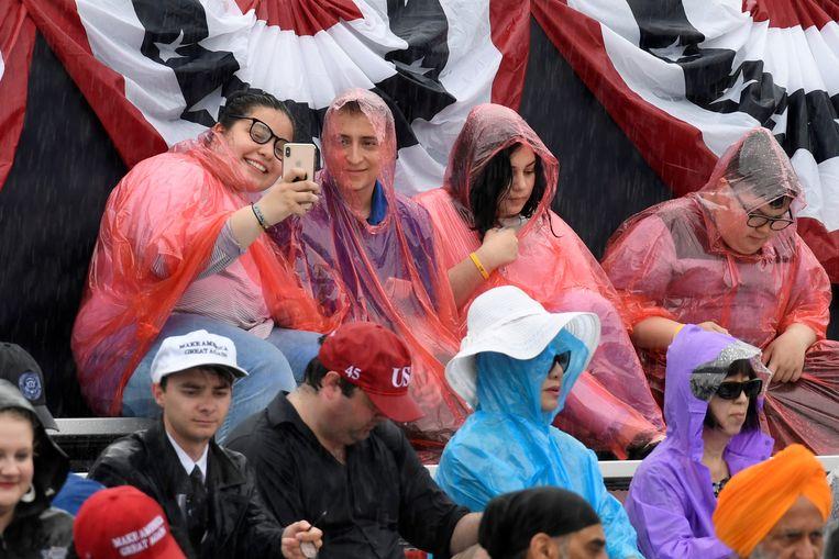 Mensen trotseren de regen om Trump live te horen speechen bij het Lincoln Memorial in Washington. Beeld REUTERS
