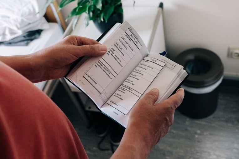 Elke patiënt in de Antwerpse Korsakov-kliniek heeft een boekje waarin alles wat ze dagelijks moeten doen, opgeschreven staat. Omdat hun geheugen hen voortdurend in de steek laat. 'Het kan eindeloos lang duren vooraleer ze nieuwe gezichten onthouden.' Beeld Wouter Van Vooren