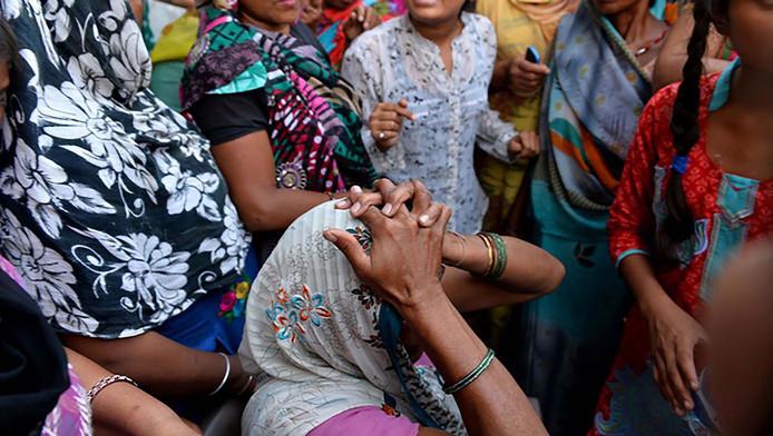 De grootmoeder van een verkracht meisje tussen protestvoerders in New Delhi.