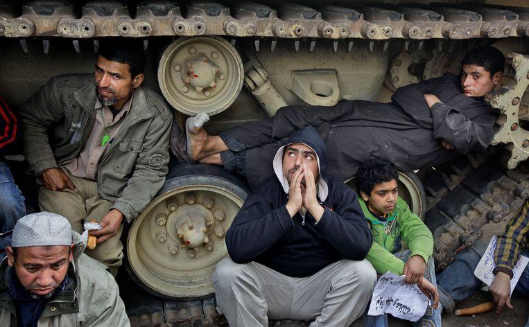 Demonstranten zitten en liggen in de rupsbanden van tanks van het Egyptische leger op het Tahrirplein. Dat doen ze zowel om te voorkomen dat de tanks ingezet kunnen worden als om te schuilen tegen de regen. Beeld AP