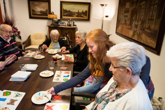 Simone helpt een groep ouderen in woonzorgcentrum Alphonsus tijdens het plaatjeskienen.