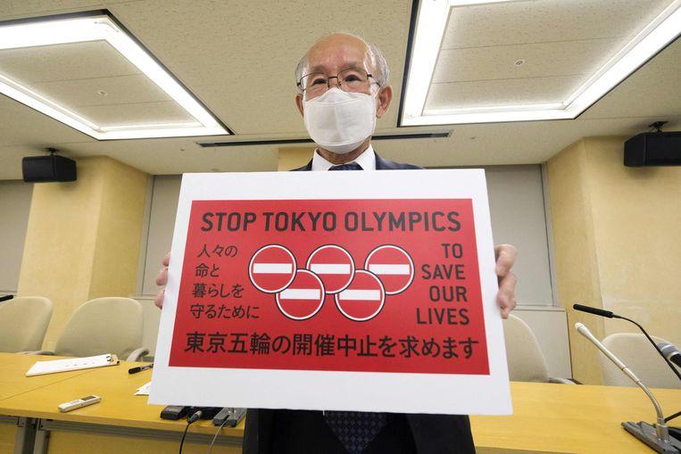 Kenji Utsunomiya, een Japanse advocaat en politicus, poseert met een protestbord vrijdag. Hij heeft dan net een petitie aan de gemeente Tokio overhandigd uit verzet tegen de Spelen. Beeld AFP