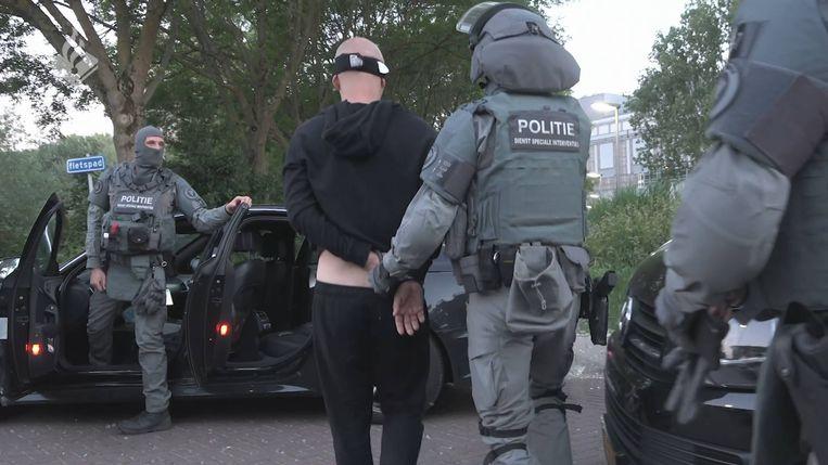 Een van de in Nederland gearresteerde verdachten wordt afgevoerd. Beeld Politie