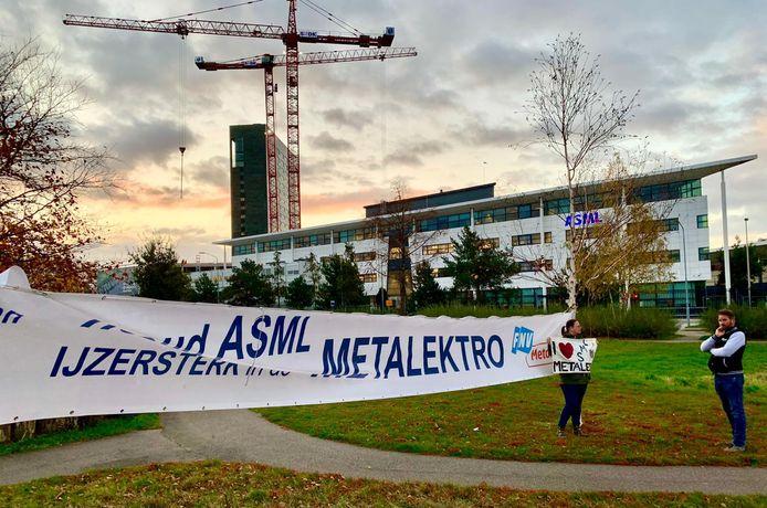 Enkele kaderleden van FNV Vakmensen staan met een spandoek bij de entree van ASML.