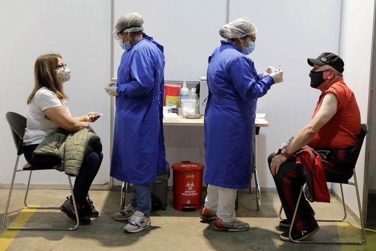Twee mensen krijgen een coronavaccinatie in Bogotá, Colombia. Beeld EPA