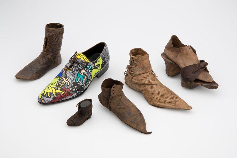 Middeleeuwse schoenen uit het Dordrechts Museum met tweede van links hedendaags op Middeleeuwse motieven geïnspireerd ontwerp van kunstenaar Pieter Zandvliet. Uiterst rechts houten trippen met leren wreefband. Beeld Jorgen Snoep