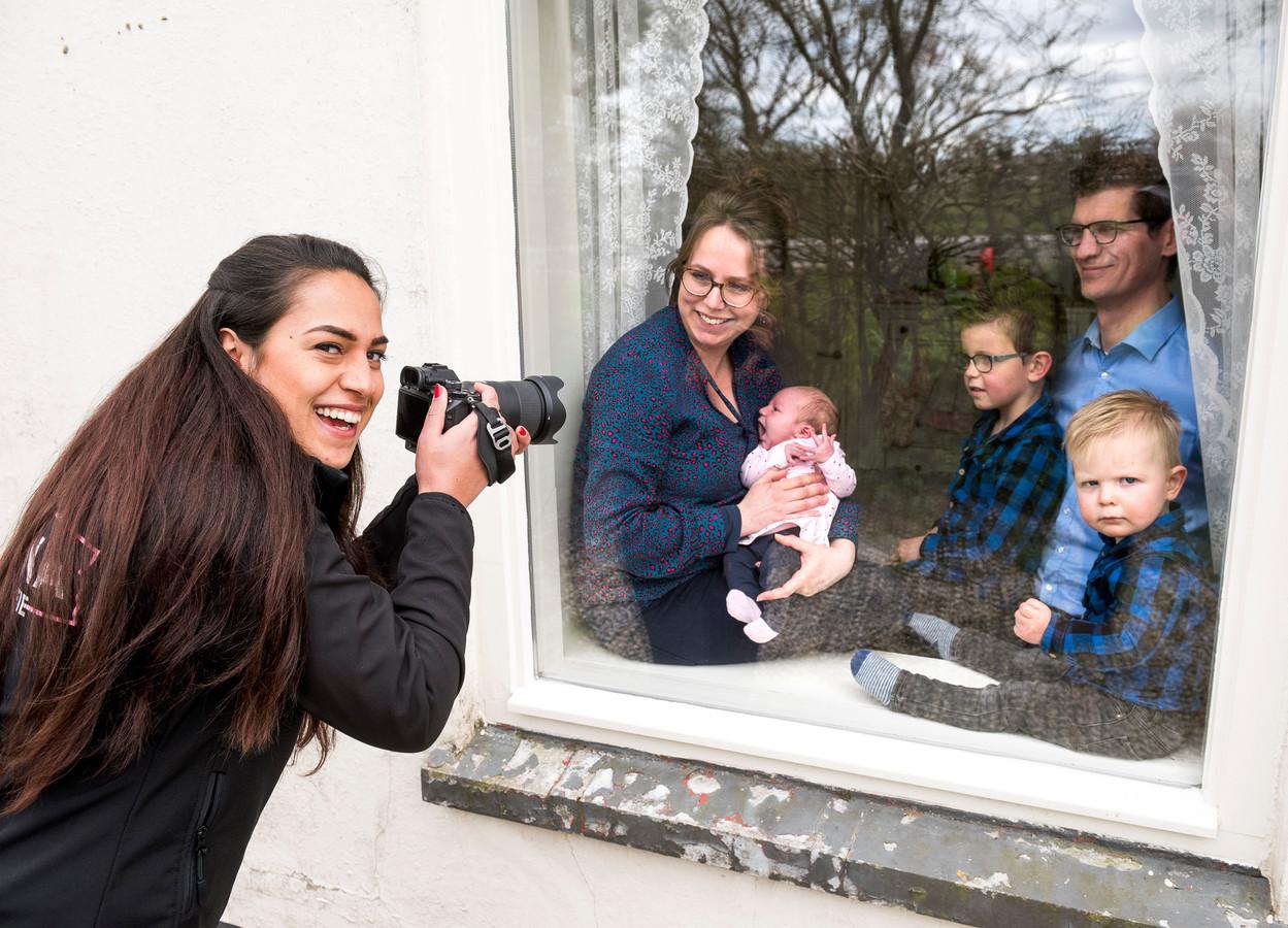 Fotografe Joanna Blankenburgh maakt portretfoto's van de familie Hoogendoorn, veilig achter het raam.
