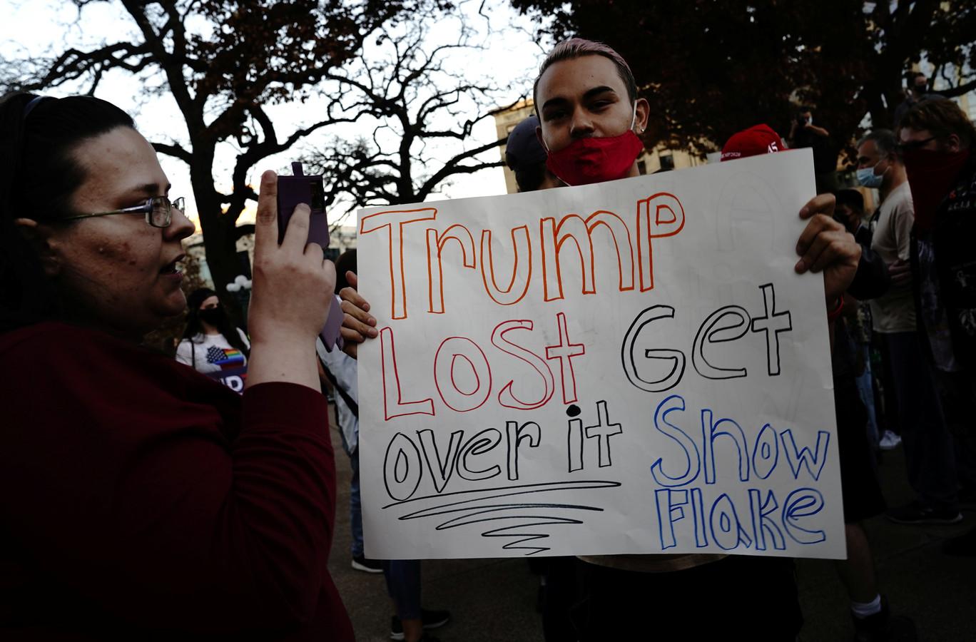 Biden-aanhangers met een bordje met de tekst 'Trump heeft verloren, zet je erover, snowflake' (een term voor iemand die snel op z'n tenen getrapt is, wordt vaak gebruikt door Republikeinen om Democraten te omschrijven). De aanhangers demonstreren aan het Wisconsin State Capitol in Madison, Wisconsin.