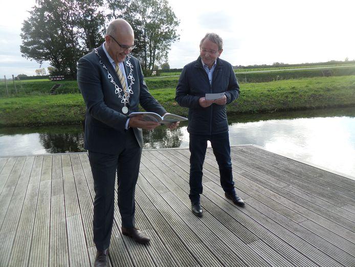 Burgemeester Ligtenberg bekijkt het boek van Altenatuur. Rechts Jaap van Diggelen, voorzitter van de natuurbeschermingsvereniging