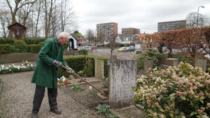 Vrijwilliger J.C. Moers van de parochie is bezig met schoffelwerk. Sinds jaar en dag onderhoudt hij de begraafplaats.