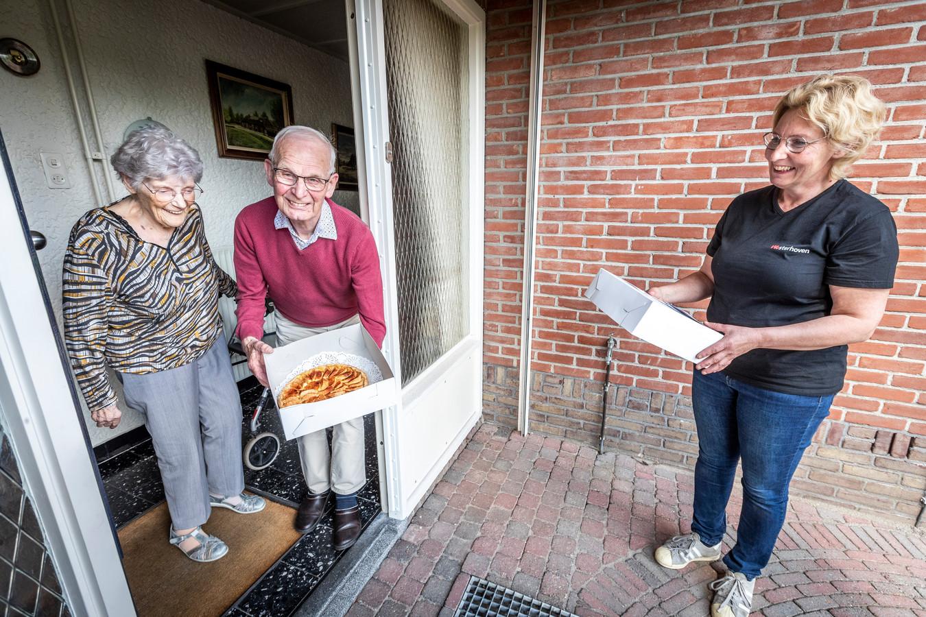 Kees en Maria Schellens krijgen een appeltaart van Petrie Verspaandonk van Wij WEsterhoven.