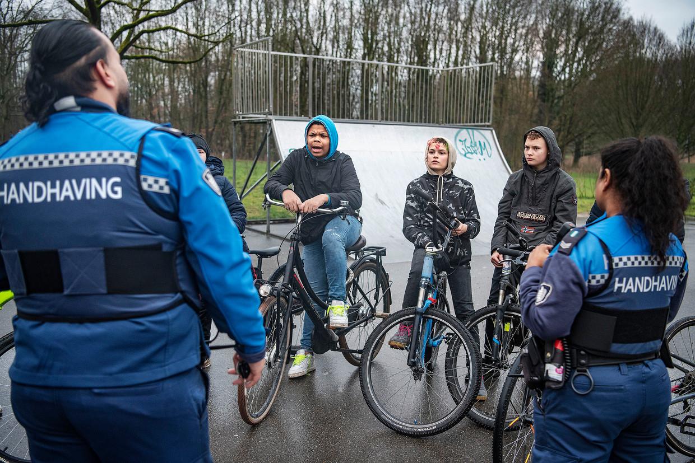 Handhavers Sharmila Oedietram en Rewin Soekhai spreken met een groepje tieners over het naleven van de coronaregels in het park de Twee Heuvels in Rotterdam. Beeld Guus Dubbelman / de Volkskrant