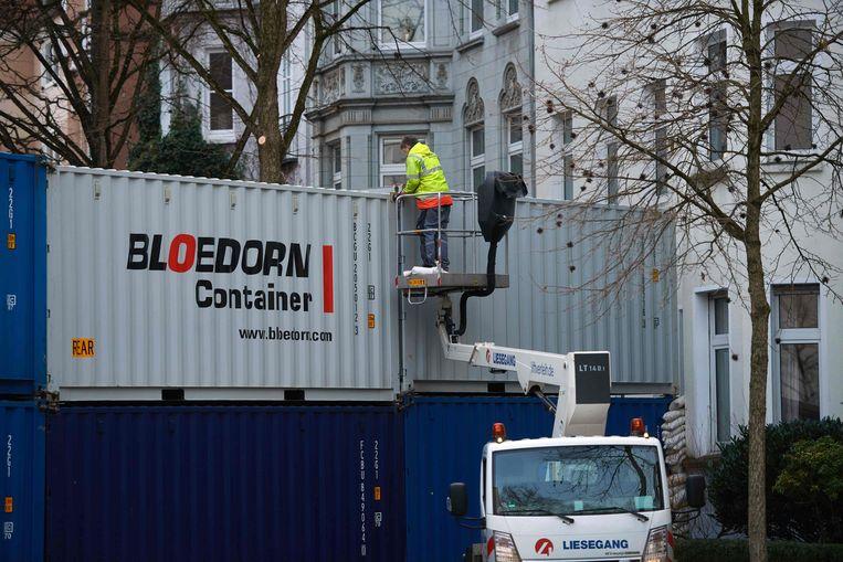 Een muur van containers wordt opgebouwd in Dortmund om huizen te beschermen tegen de WOII-bommen. Beeld AFP
