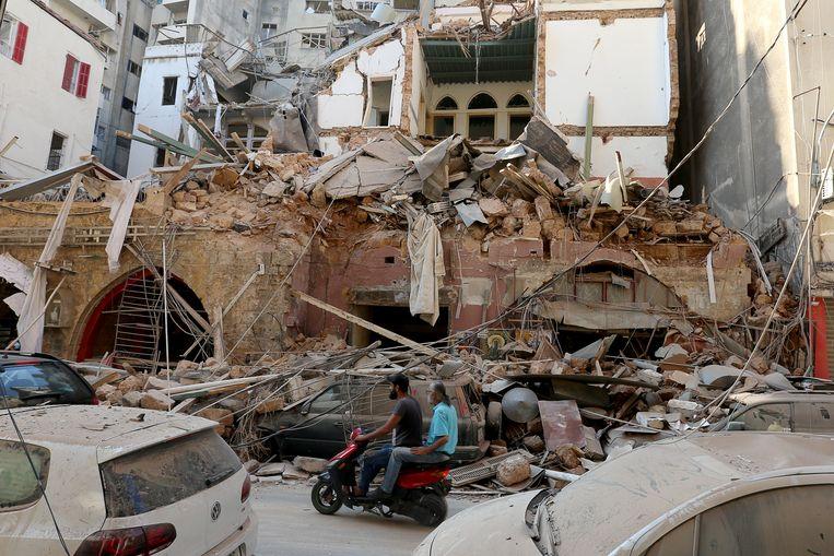 Twee inwoners rijden tussen de vernielde straten. Beeld REUTERS