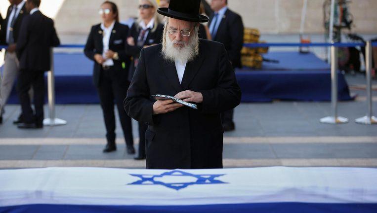 Ultra-orthodox parlementslid bidt bij de kist van Peres. Beeld reuters