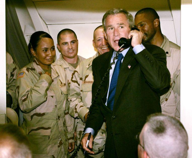 De voormalige president George W. Bush spreekt in september 2004 via een intercom van een vliegtuig Amerikaanse soldaten toe die op het punt staan naar Irak te gaan.  Beeld Reuters