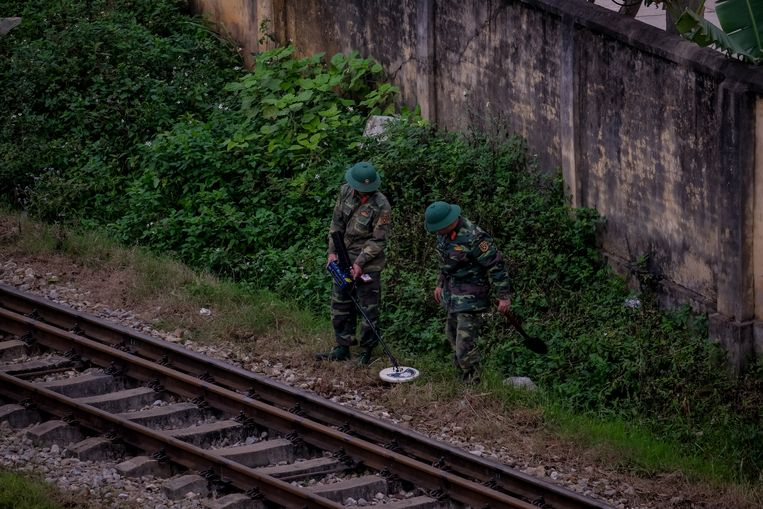 Militairen zoeken naar verdachte voorwerpen langs het spoor ter voorbereiding  op de aankomst van Kim Jong-un.  Beeld Getty Images